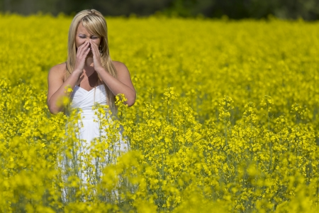 A blonde model in a field of flowers with allergies Archivio Fotografico