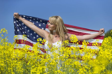 A blonde model in a field of flowers with the American flag photo