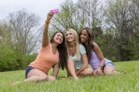 Three young women take a group photo as they enjoy a day at the park. photo