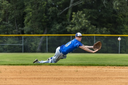 A young male plays baseball on a summer day