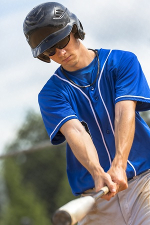 A young male plays baseball on a summer day photo