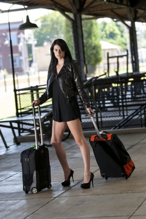 A dark haired model posing at a train station photo