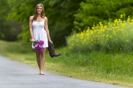 A brunette model walking down a country road photo