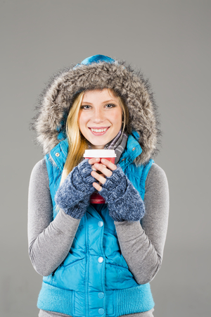A blonde model poses in a studio environment wearing winter clothing drinking a hot beverage photo