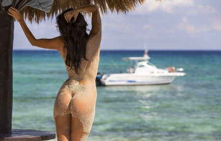 A nude model poses on a beach