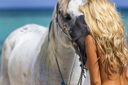 A nude model on horseback on a caribbean beach