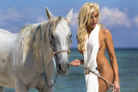 Een naakt model te paard op een Caribische strand