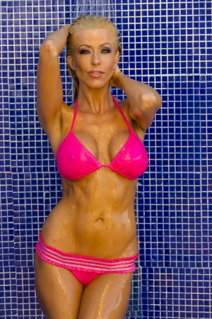 A bikini model posing in an outdoor shower