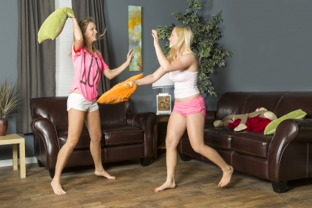 Two young girls pillow fight during a slumber party photo
