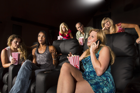A woman on the phone with a group of people watching a movie showing emotion photo