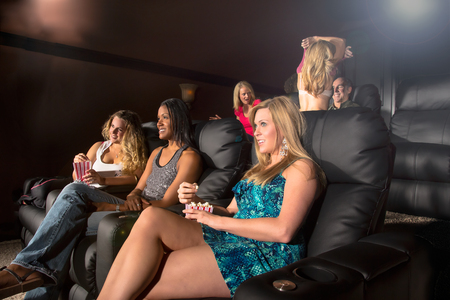 A group of people watching a movie showing emotion while a couple make out in the back photo