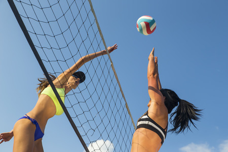 Two female athletes playing beach volleyball 스톡 콘텐츠