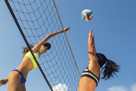 pelota de voley: Dos mujeres atletas que juegan a voleibol de playa