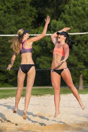 beach volley: Two female athletes playing beach volleyball Stock Photo