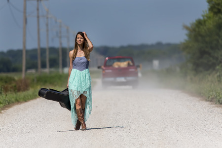 guitar case: Female walking down a dirt road hitchhiking with a guitar case Stock Photo