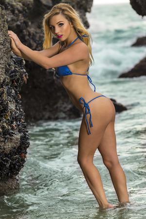 A bikini model poses on a beach Standard-Bild