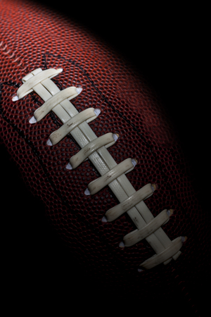 close up of an american football against a black background Archivio Fotografico