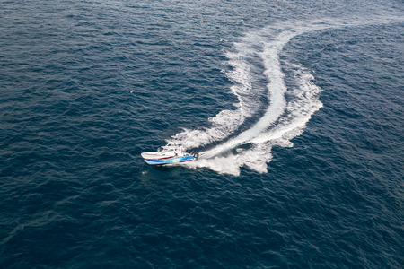Fast motorboat with splash and wake on an ocean