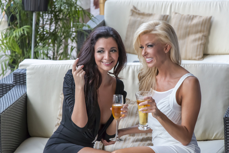 Two women gossip while having cocktails