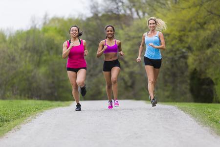Three young women jogging in a park Archivio Fotografico