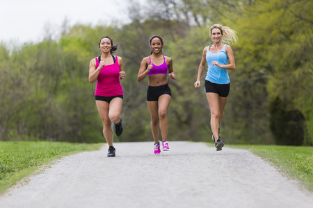 Three young women jogging in a park Banque d'images