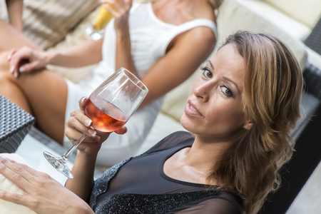 Two women gossip while having cocktails photo