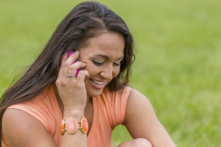 A young brunette model sits in a park talking on a cellular telephone