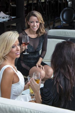 Beautiful women gossip while having cocktails photo