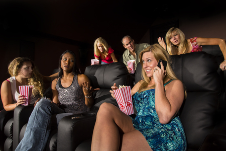 patron: A group of people watching a movie showing emotion as a patron talks on a cellphone