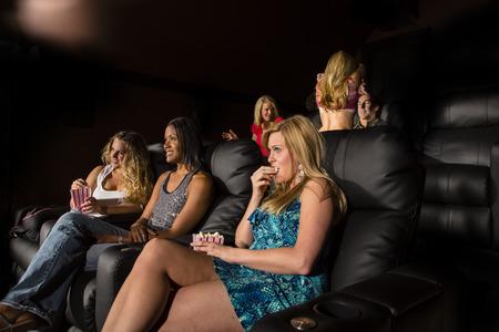Un grupo de personas viendo una película que muestra la emoción como una pareja hace en la parte posterior