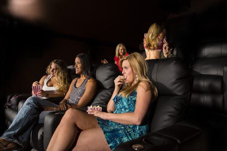 A group of people watching a movie showing emotion as a couple makes out in the back