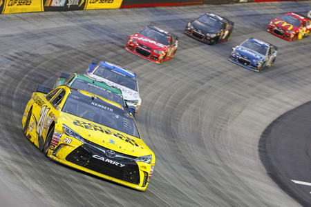 racing car: Bristol, TN - Apr 19, 2015:  Matt Kenseth (20) brings his race car through the turns during the Food City 500 race at the Bristol Motor Speedway in Bristol, TN.