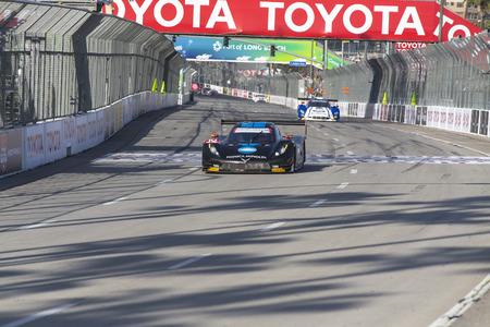 patron: Long Beach, CA - Apr 18, 2015:  The Konica Minolta Chevrolet crosses the finish line at the Tequila Patron Sports Car Racing Showcase at Long Beach Grand Prix in Long Beach, CA.