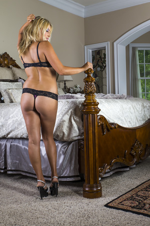 A blonde model poses in lingerie in a home environment