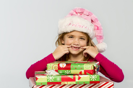 A little girl in a studio environment with presents missing her two front teeth Standard-Bild