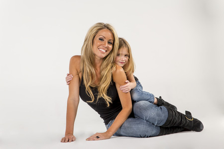 A mother and daughter pose in a studio environment photo