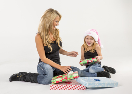 A mother and daughter pose in a studio environment with presents photo