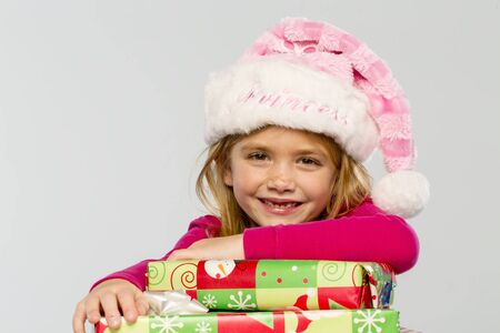 A little girl in a studio environment with presents missing her two front teeth photo