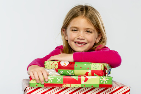 A little girl in a studio environment with presents missing her two front teeth Reklamní fotografie
