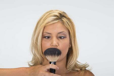 blonde minority: A pretty ethnic blonde model having makeup applied in a studio environment.