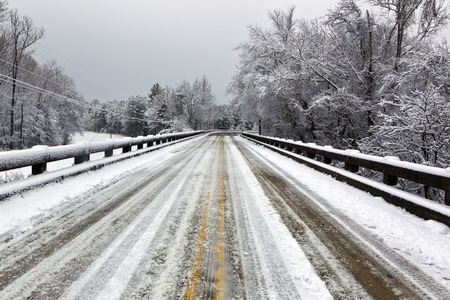 drenched: A winter landscape show snow falling on a snow drenched bridge