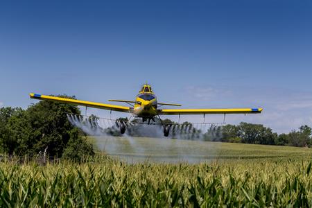 농작물 살포기는 식물의 들판에 화학 물질을 적용합니다.