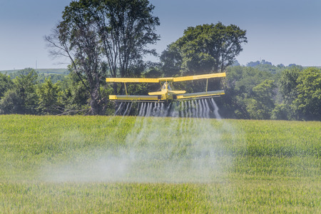 iowa agriculture: A crop duster applies chemicals to a field of vegetation.