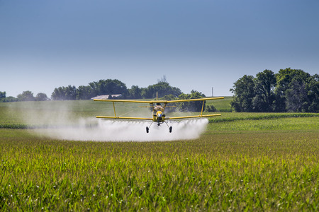 A crop duster applies chemicals to a field of vegetation. Stock Photo - 48092055