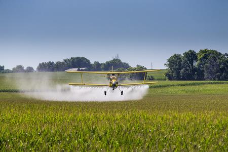 Een gewas duster geldt chemicaliën om een gebied van de vegetatie.