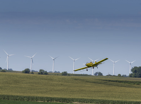 fungicide: A crop duster applies chemicals to a field of vegetation.