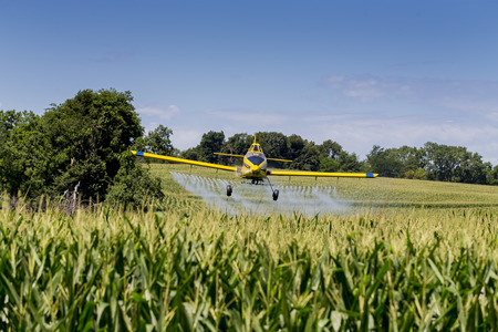 sprayer: A crop duster applies chemicals to a field of vegetation.