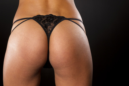 tan woman: Portrait of a model with a black thong in a studio environment Stock Photo