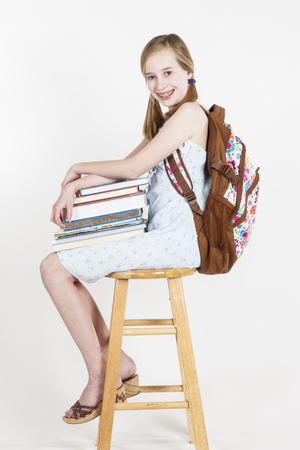 composition book: Portrait of friendly school girl student with backpack, sitting on a stool, holding notebooks and composition book
