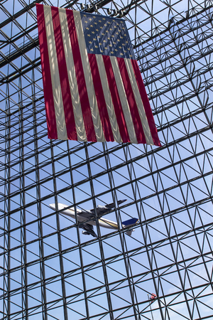 faa: A jetliner taking off from an airport with an American flag in the foreground Editorial